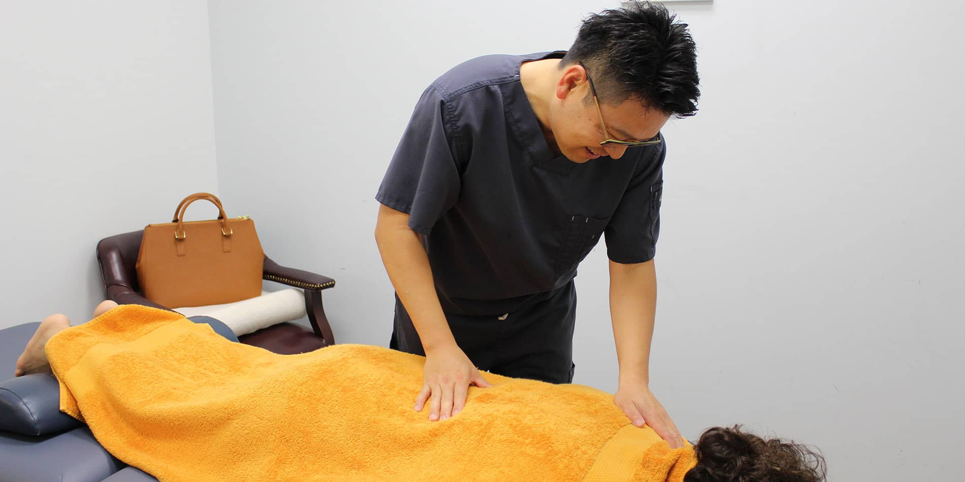 Dr. Cho showcasing state of the art technology for deep-tissue massage therapy and chiropractic care for optimum health and body awareness.